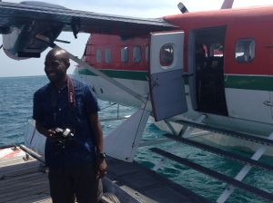 Jay standing by a seaplane, camera in hand